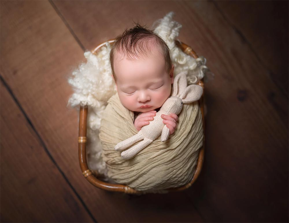 Newborn baby being photographed by New Born Photographer Moss & Ivy Photography